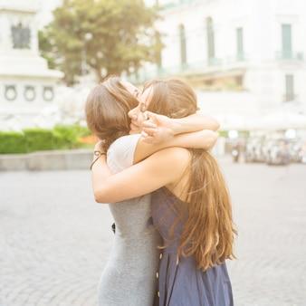 屋外でお互いを抱き合っている2人の女性の友人