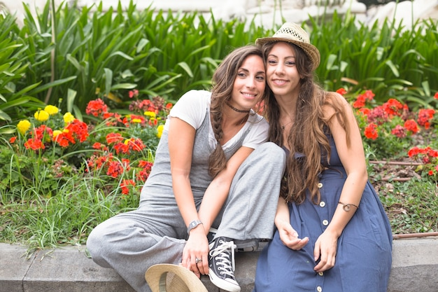 庭に座っている2人の女性の友人の笑顔の肖像