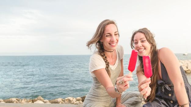 赤いキャンディーを示す海岸に座っている2人の女性の友達を笑って