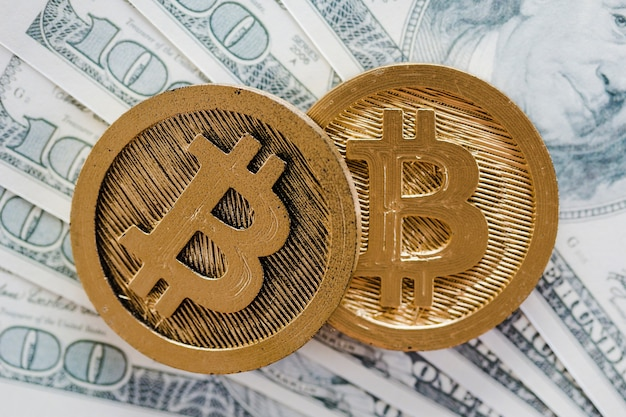 米ドル通貨の銀行券の上に2つのビットコイン