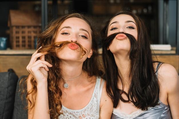 2人の女性の友達が髪を使って偽の口髭を作る