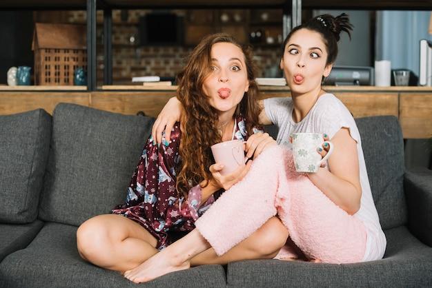 面白い顔を作る舌を突き出す2人の女性の友人