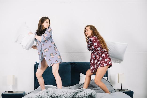 家庭でベッドで戦っている2人の若い女性の枕