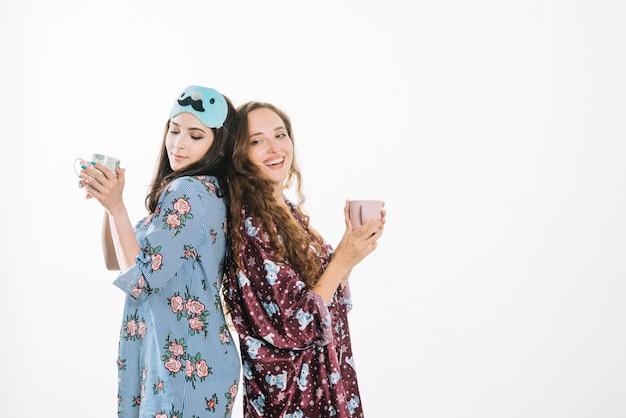 2人の女性の友人がコーヒーを飲んで背中合わせに立っている