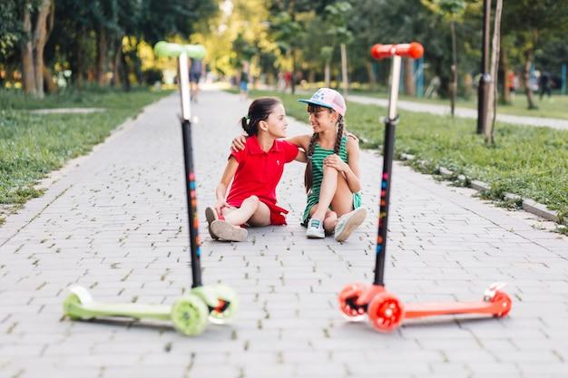 歩道に一緒に座っている2人の女性の友人の前でスクーターを押す