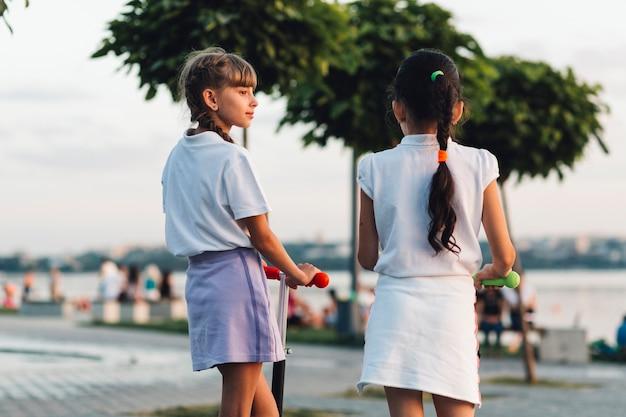 プッシュスクーターで2人の女の子の背面図