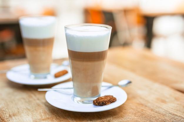 木製テーブルにスプーンとソーサー付きの2つのカプチーノコーヒーメガネ