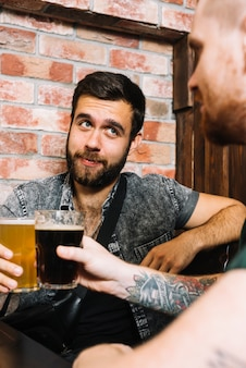 2人の男性の友人がアルコール飲料をトースト