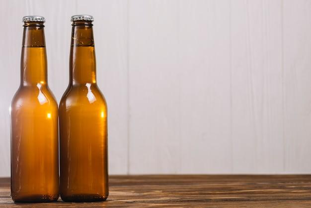 木製の表面に2つのビール瓶