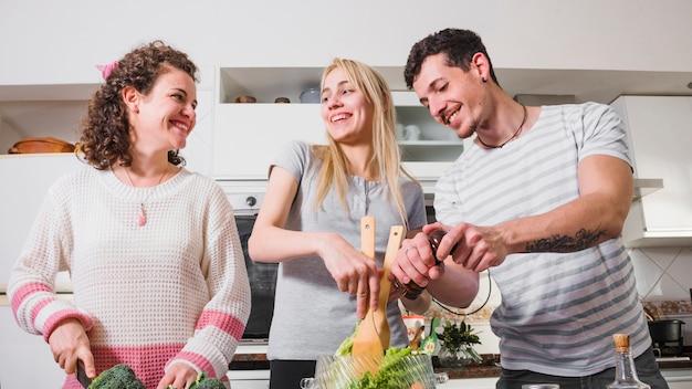 2人の女性の友人と彼女の男は台所でサラダを準備する