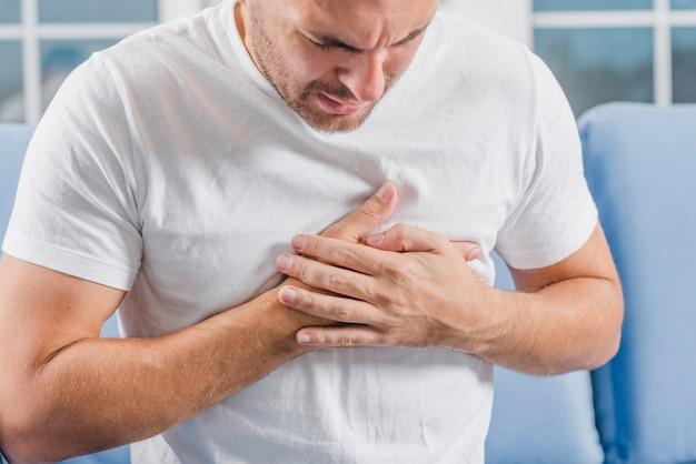 2つの手で彼の心に触れる心臓発作の症状を持つ男性のクローズアップ