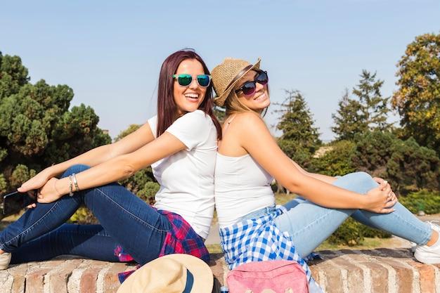 屋外で背中合わせに座っている2つの笑顔の女性の友達