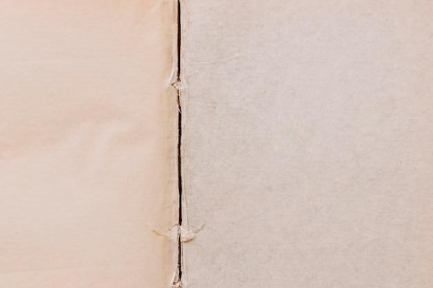 古い2つの紙テクスチャ表面の背景に破れた線
