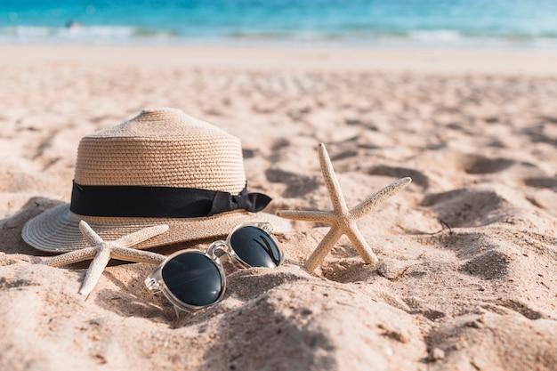 砂の上に帽子を入れた2つのスターフィッシュ