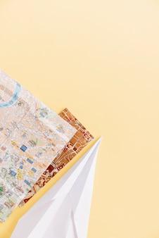 背景の角に手作り紙飛行機を持つ2つの都市地図