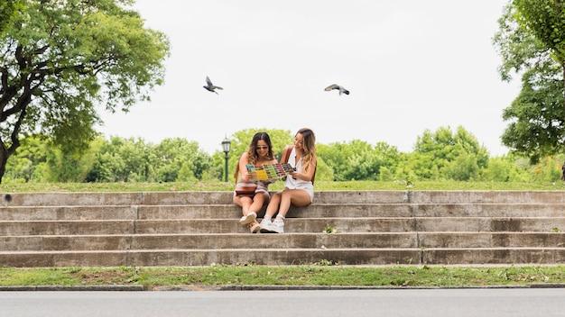 公園の地図を見て階段の上に座っている2人の女性観光客