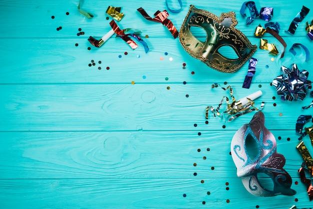 青いテーブルの上の紙吹雪と2つの仮装カーニバルマスク