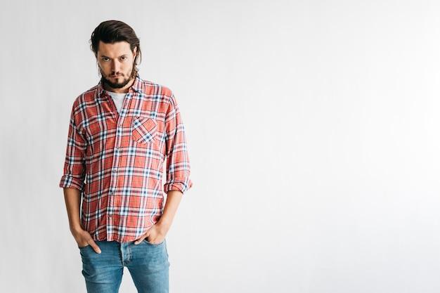 彼のポケットに白い背景で隔離の2つの手で市松模様のシャツで怒っている人