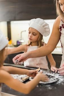 母と2人の娘が台所でクッキーを準備します。