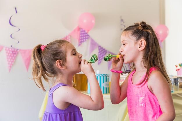 パーティーホーンを吹く2つの小さな女友達の側面図