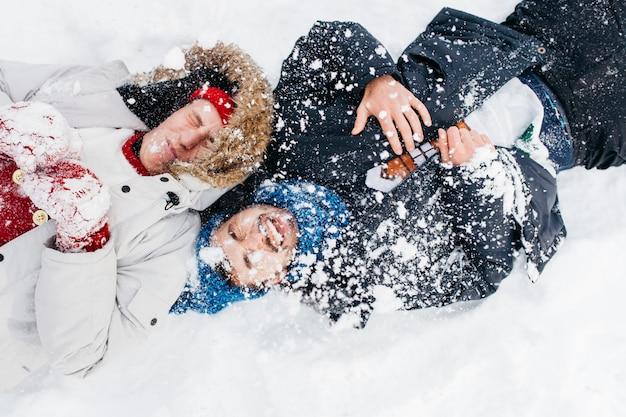 雪で覆われた横になっている2人の男性