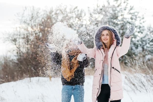 2人の女性が空気中に雪を投げる