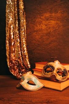 暗い織り目加工の背景に対して本を持つ2つのベネチアンカーニバルマスクの静物