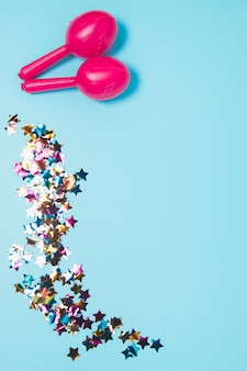 青い背景にカラフルな星形の紙吹雪とピンクの2つのマラカス