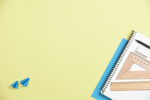 黄色の背景に対してオフィス文房具を持つ2つの折り紙飛行機