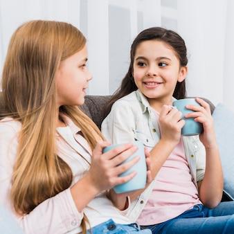 手でコーヒーのマグカップを持ってお互いを見てソファの上に座っている2人の友人のクローズアップ