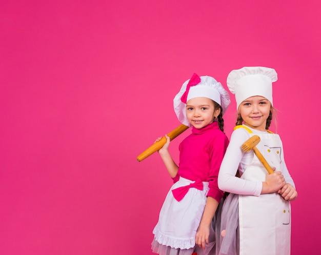 2人の女の子が台所用品と一緒に立って調理します