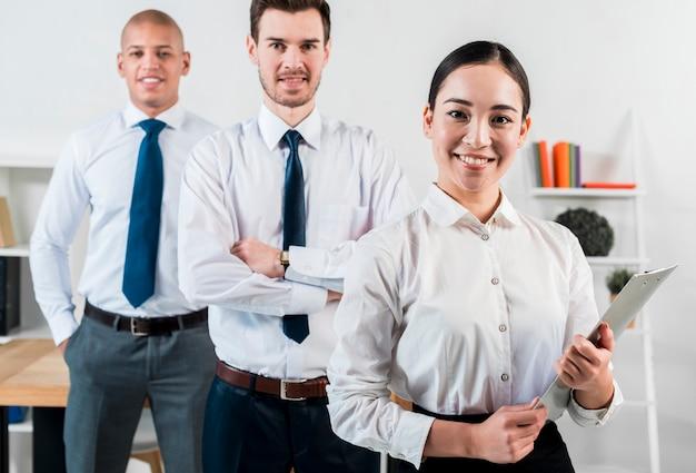 Портрет азиатской коммерсантки держа доску сзажимом для бумаги в руке стоя перед бизнесменом 2