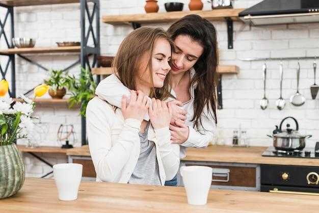 2つのコーヒーカップと木製のテーブルの前でロマンチックな若いカップル