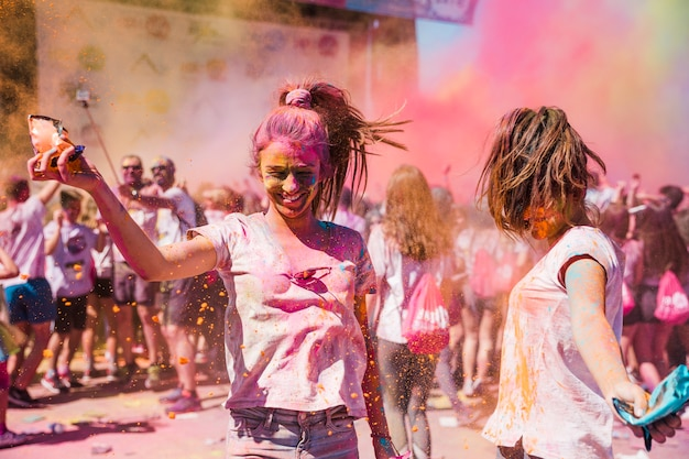 2人の若い女性が遊んで、ホーリー色を楽しんで