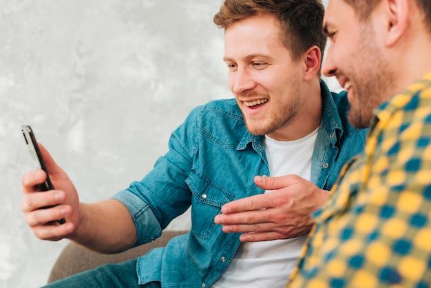 一緒に携帯電話を見て座っている2人の男性の友人のクローズアップ