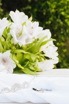 2つの結婚指輪とテーブルの上の美しい花の花束とスカーフの冠