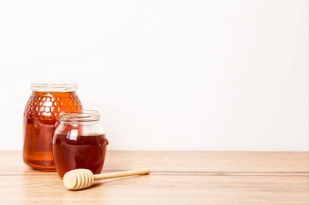 木製の机の上の蜂蜜ディッパーと蜂蜜の2つの瓶