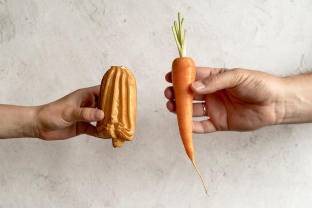 健康的な食品と不健康な食品を比較する2人の手