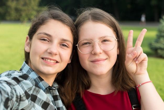 2つの笑みを浮かべて学校の女の子の肖像画を閉じる