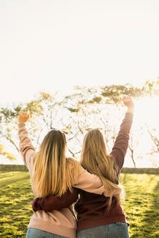 日光の下で2人の女性が後ろから抱擁します。