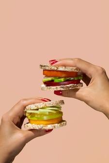 2つの野菜ハンバーガーを保持しているクローズアップ人