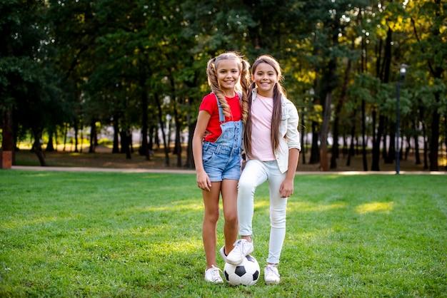 屋外のサッカーボールを持つ2人の女の子