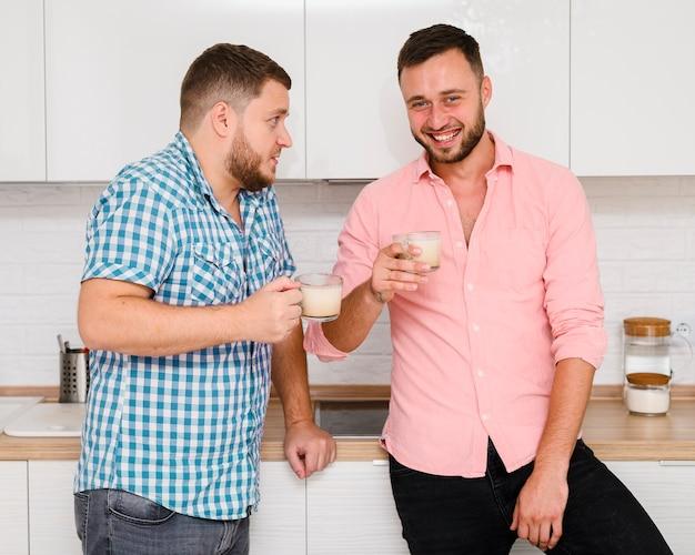 キッチンでコーヒーを飲みながら2人の若い男性