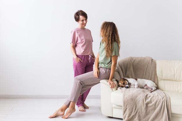 かわいい犬と自宅で2人の女性の友人や姉妹。検疫、隔離、コロナウイルスの世界的流行。家にいる。