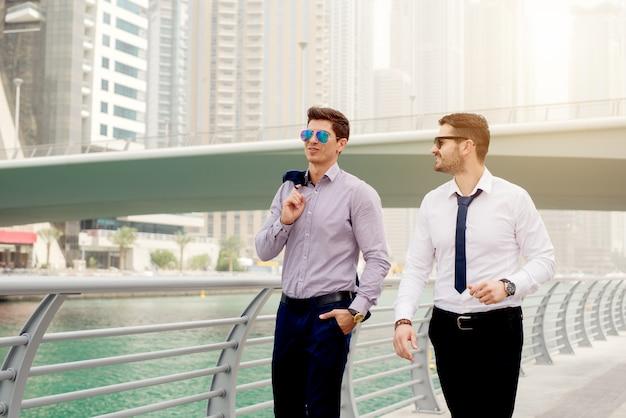 ウォーキングとドバイマリーナで話している2つのビジネスマン。