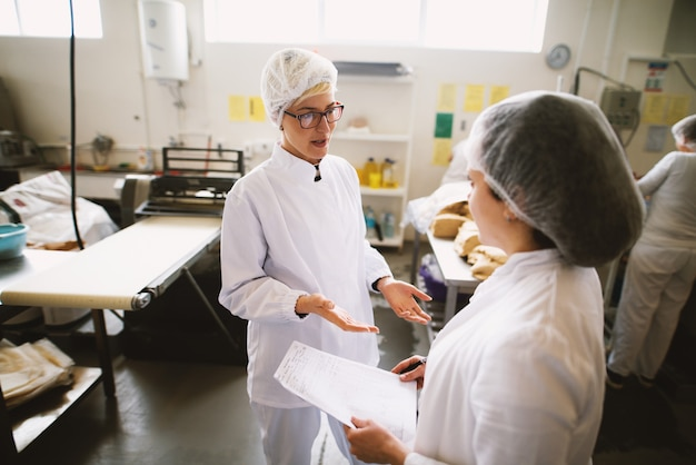 大きなパン屋に立っている間話している無菌布で2人の女性労働者。