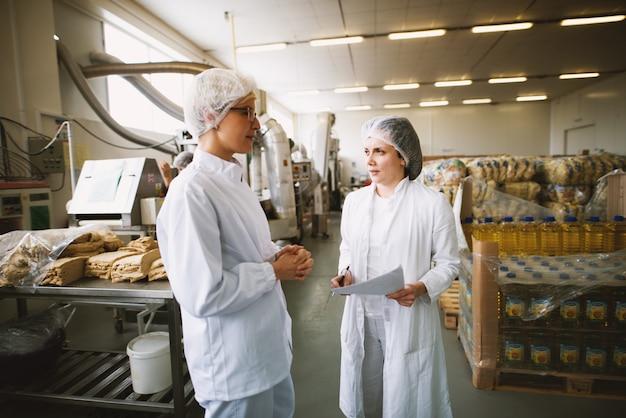 無菌の布を着た2人の若い美しい女性労働者が、生産ラインと倉庫の近くのベーカリーで統計を話し合っています。