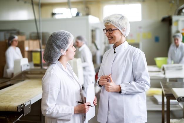 食品工場に立ちながら議論する2人の女性労働者。