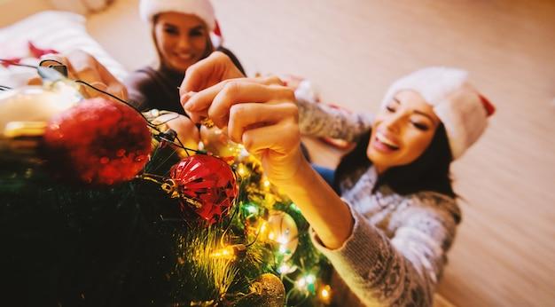 クリスマスツリーを飾る2人の女性の空撮。