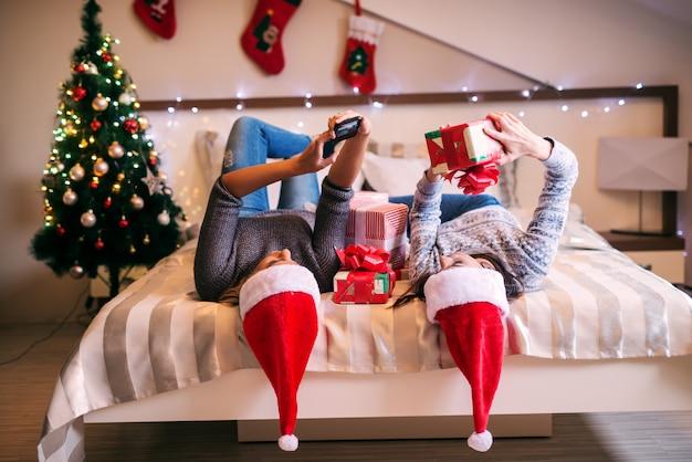 頭にクリスマス帽子をかぶってベッドに横になっている2人の若い女の子とその周りにプレゼント。